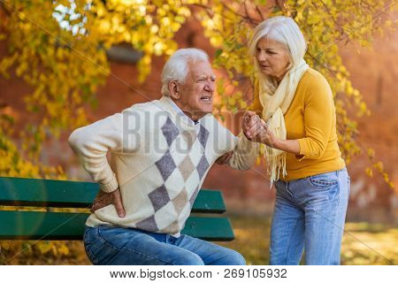 Senior woman helping senior man who has a back pain