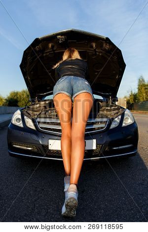 Photo Of Back Of Young Woman In Short Shorts Mending Black Car In Summer Day On Street
