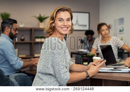 Mature businesswoman using smartphone during business meeting. Successful business woman checking mails and replying from mobile while looking at camera. Portrait of smiling casual lady at office.