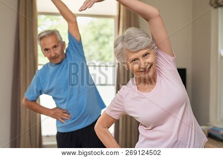 Portrait of happy smiling senior couple with arms raised doing stretching exercise at home. Old man and elderly woman practicing at home during early morning. Retired couple doing aerobics workout.