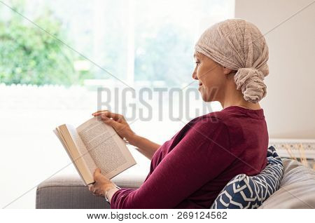 Cancer woman with headscarf reading a book on couch at home. Side view of smiling senior woman suffering from tumor relaxing at home. Mature happy woman at home sitting near window reading a book.