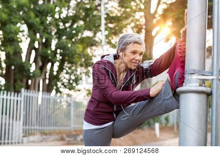 Senior woman using lamp post as support to stretching legs for warm up before running. Sporty woman stretching legs in the city street. Mature fitness lady warming up outdoor.