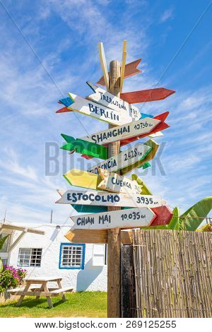 Wooden Pole Guidepost With Multiple Destinations Of The World On Arrows Sticks (white, Yellow, Red A