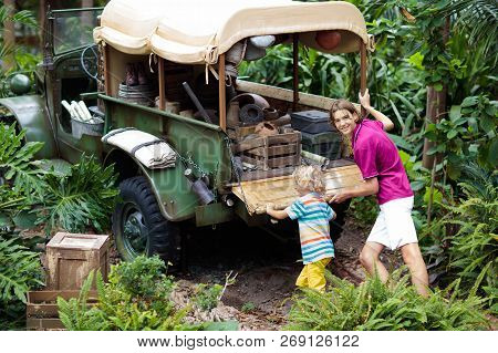 Man and child push car stuck in mud in jungle. Family pushing off road vehicle stuck in muddy dirt terrain in tropical forest. Island adventure drive. poster