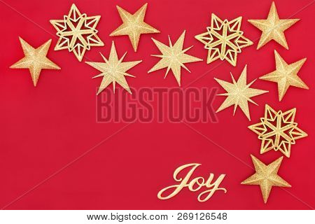 Christmas abstract background with gold glitter star bauble decorations and joy sign on red with copy space. Traditional Christmas greeting card for the festive season.