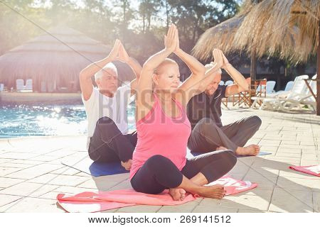 Three seniors at the spa hotel by the pool doing yoga exercise with clasped hands