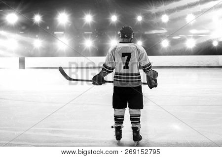 Hockey player with hockey stick standing on rink against composite image of blue spotlight