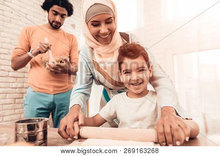 Happy Arabian Family Cooking Food In Kitchen. Muslim Family. Smiling Boy. Young Arabian Woman. Moder