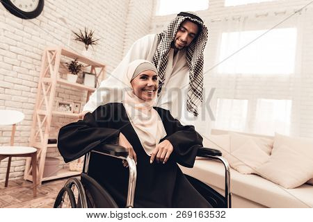 Young Arabian Woman On Wheelchair With Husband. Arabian Family Concept. Sitting On Wheelchair. Disab