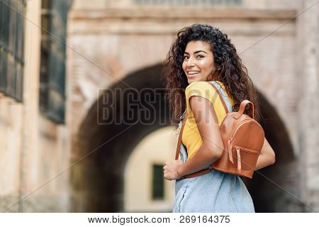 Rear View Of Young Arab Woman With Backpack Outdoors. Traveler Girl In Casual Clothes In The Street.