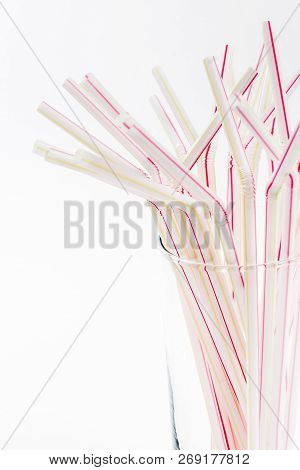 Red Stripped Straws In Glass On White