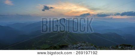 Fantastic Sunrise Or Sunset Over Green Mountain Ridge Covered With Dense Blue Fog. Bright Orange Sun