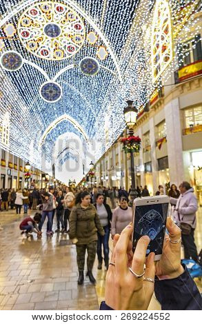 Malaga, Spain - December 9,2017: Woman Takes A Photo Of Christmas Decorations On Calle Marques De La
