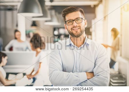 Portrait Of Young Confident Man Leader Standing In Office. New Start Up Business Concept.
