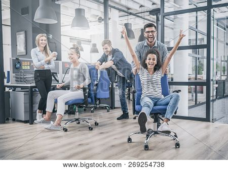 Young Cheerful Business People Dressed In Casual Clothing Are Having Fun On Rowing Chairs In A Moder