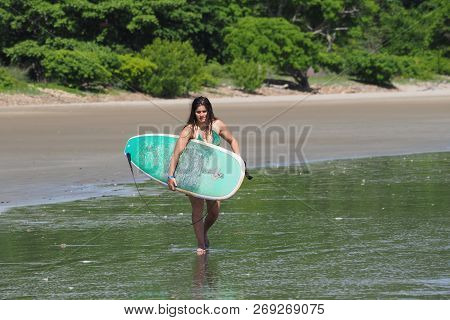 Playa Hermosa, Nicaragua 06-13-2017 Young Woman Surfs On Playa Hermosa On A Sunny Summer Day.