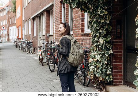 Tourist with a backpack is looking for booked online accommodation in an unfamiliar city. Or a student girl with a backpack is walking through the city. poster