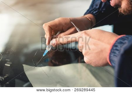 Close-up Of A Hands Of Professional Windshield Repairman Fills A Crack In The Glass With A Special P