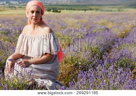 Woman in light dress and red head shawl sits squatted on lavender field on sunny day.