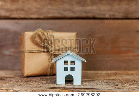 Miniature White Toy House And Gift Box Wrapped Craft Paper On Old Shabby Rustic Wooden Background. M