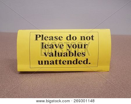 yellow please do not leave your valuables unattended sign on table poster