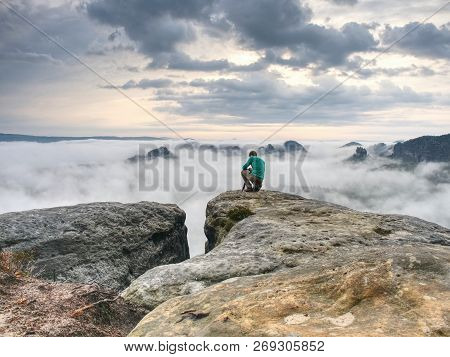 Hiker And Photo Enthusiast Stay With Tripod On Cliff. Peak With Two Men Taking Photos In Autumn Morn