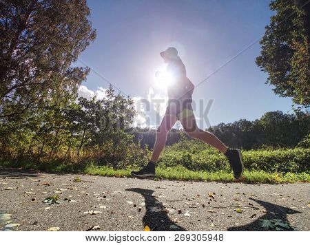 Exigent Physical Training. The Athlete Runs Fast Through Alley. Wet Asphalt With Fallen Maple And Sp