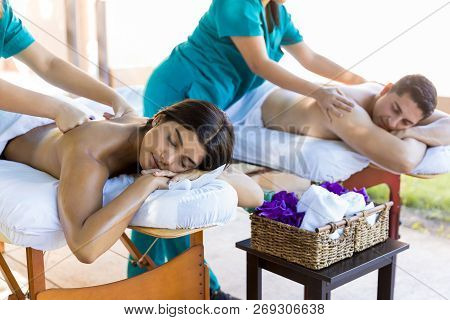Honeymoon Couple Relaxing While Getting Body Massage From Masseuses At Dayspa