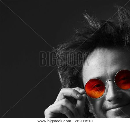 Smiling man with round hippie sunglasses and long hairs