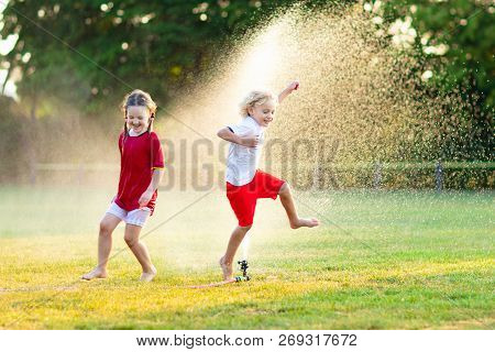 Kids Play With Water. Child With Garden Sprinkler.