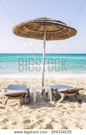 Relaxing Scene On A Breezy Day At The Tropical Beach, Two Deck Chair And Umbrella