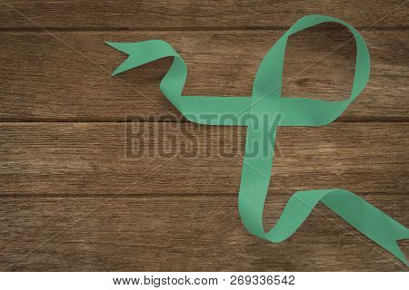 Ovarian cancer and gynecological disorders concept. Green ribbon symbolic support campaign on people living life with Ovarian cancer poster