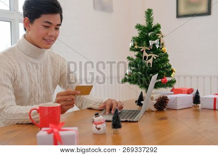 Man Holding Credit Card For Online Shopping. Male Buyer Buying Christmas Gift On Internet. New Year