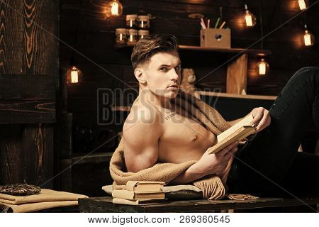 Sexy student concept. Man with muscular torso, six packs, lay near bookshelves, dark background. Smart guy with book. Student on pensive face, attractive muscular figure, holds books in hand, reads poster