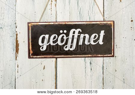 Old Metal Sign In Front Of A White Wooden Wall - Geöffnet (german Word For Open)