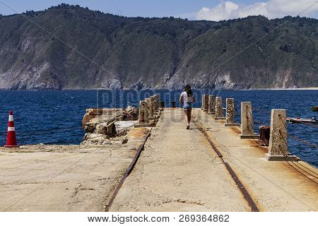 Young Girl Walking Along A Pier In Chile