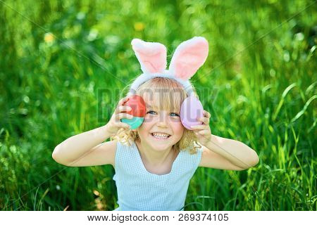 Cute Funny Girl With Easter Eggs And Bunny Ears At Garden. Easter Concept. Laughing Child At Easter