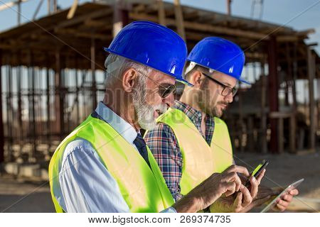 Senior Engineer And Worker Looking At Cell Phone And Tablet In Front Of Construction At Building Sit