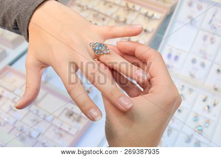 A Girl In A Jewelry Store Tries On Her Finger A Gold Ring With Diamonds On The Background Of A Shop