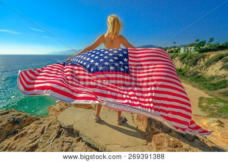 Freedom And Patriotic Concept. Woman Holding An American Flag Waving From Point Dume Promontory On M