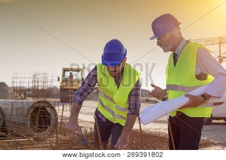 Construction Worker With Helmet Working On Reinforcement Mesh At Building Site And Engineer Talking