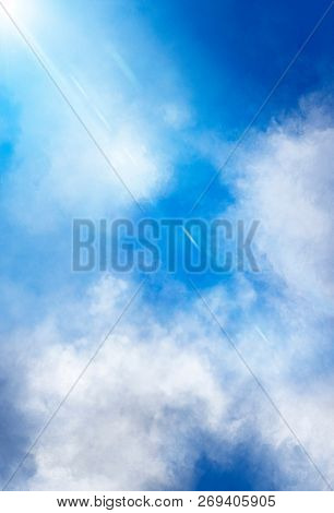Heavenly Clouds and lights background. Bright lights from above shinning down on misty soft clouds in a blue sky.