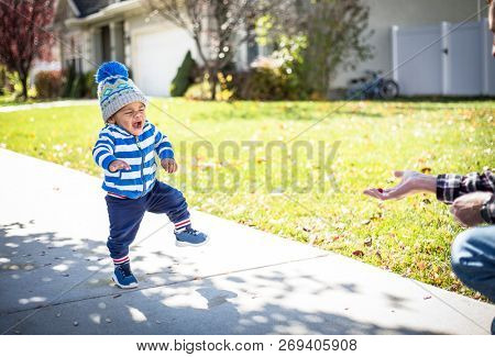 A cute little Africa American little boy learning to walk and taking big steps with an excited expression on his face. Walking towards a treat. Eyes on the prize