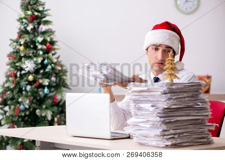 Young worker working in office on christmas shift