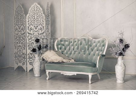 Interior with vintage furniture, retro beautiful grey sofa. White Livingroom interior.Large Antique Floor Vases with Decorative flowers.Grey sofa with pillows and blanket poster