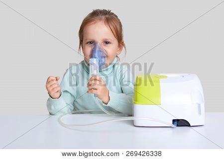Pretty small child uses nebulizer mask for inahlation, cares of health, sits at white desktop, dressed in casual jumper, isolated over white background. Little girl cures cough or pneumonia. poster