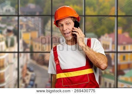 Manual Worker Talking On Cell Phone. Mature Construction Engineer Talking On Mobile Phone On Abstrac