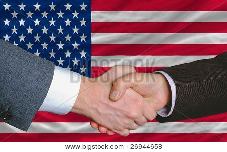 two businessmen shaking hands after good business investment agreement in america in front of flag poster