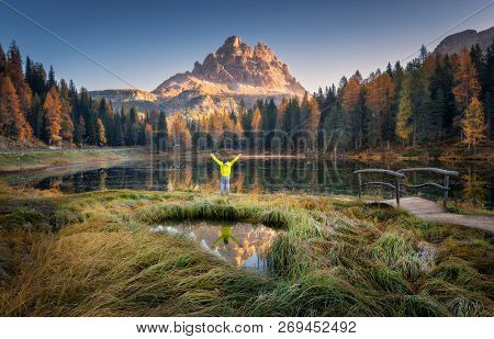 Man With Raised Up Arms On Antorno Lake With Reflection Of Tre Cime Di Lavaredo At Sunrise In Autumn