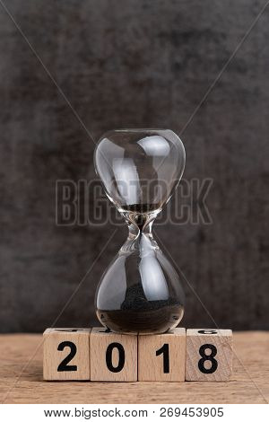 Year End 2018 Time Countdown Or Business Goals Review Concept, Hourglass Or Sandglass And Stack Of C